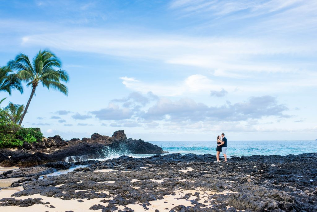 Couple embracing on Maui beach with waves and palm tree in background