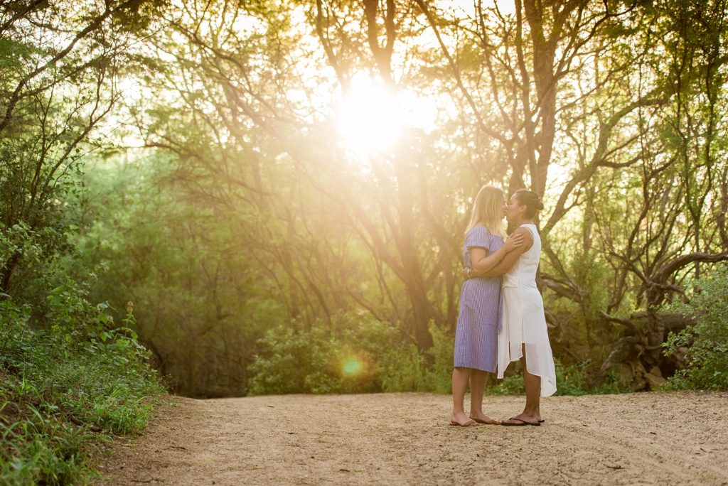 Couple kissing as sunlight streams through forest