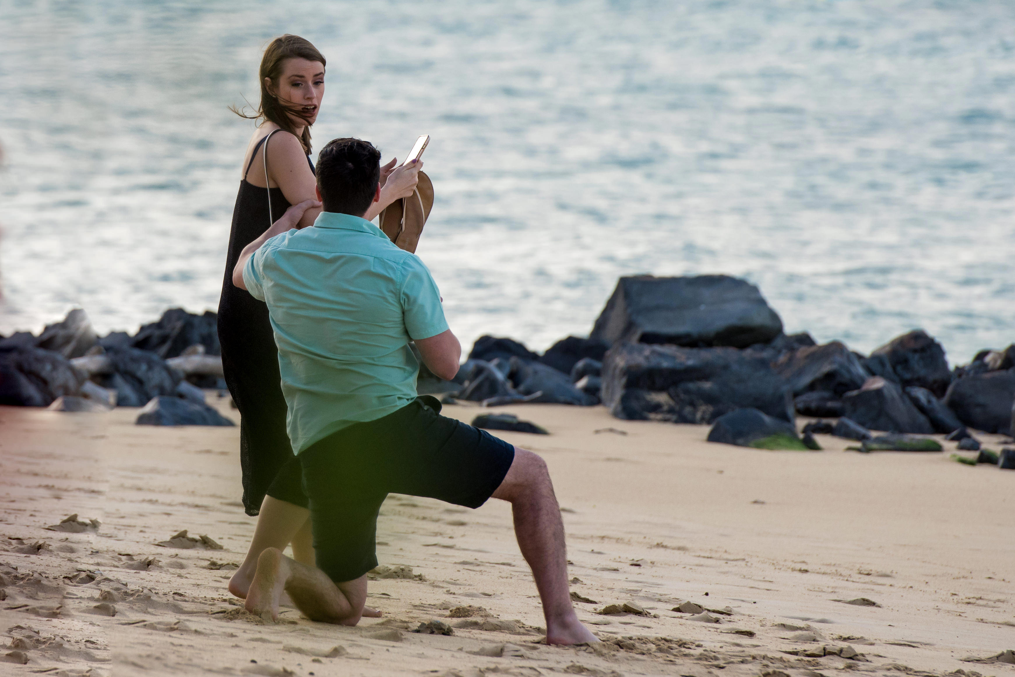 man down on one knee proposing at beach