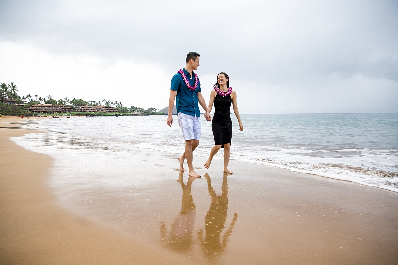 engaged couple walking on secluded beach