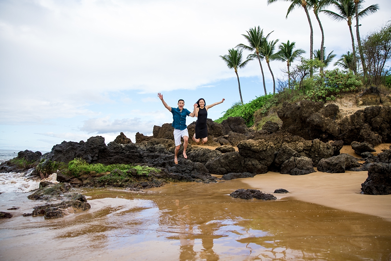 couple jumping for joy on rocky beach in maui