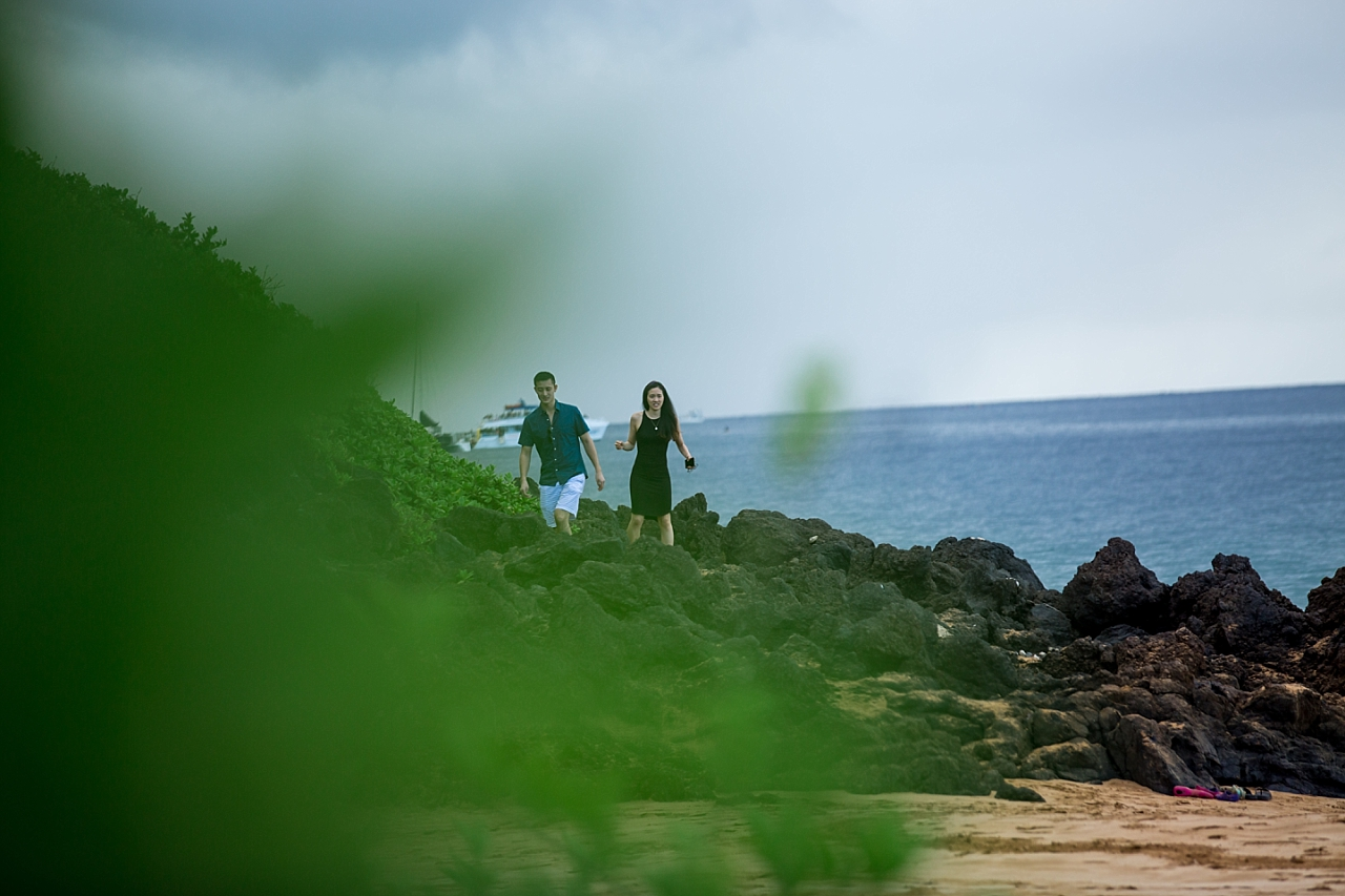 couple walking hand in hand on rocky beach in Maui