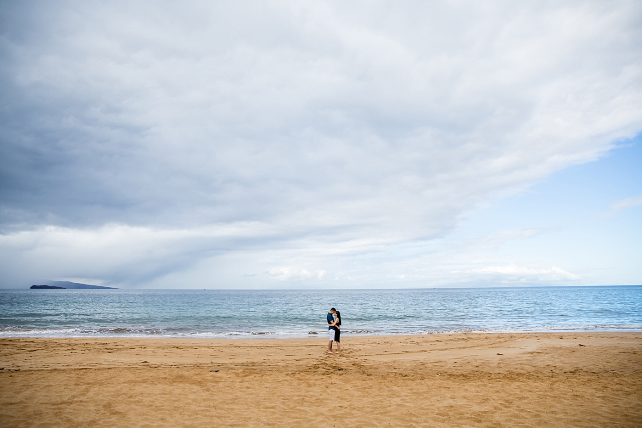 couple standing in front of the ocean after beach proposal