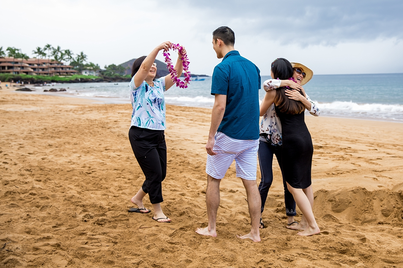 mom greeting newly engaged couple with leis on the beach