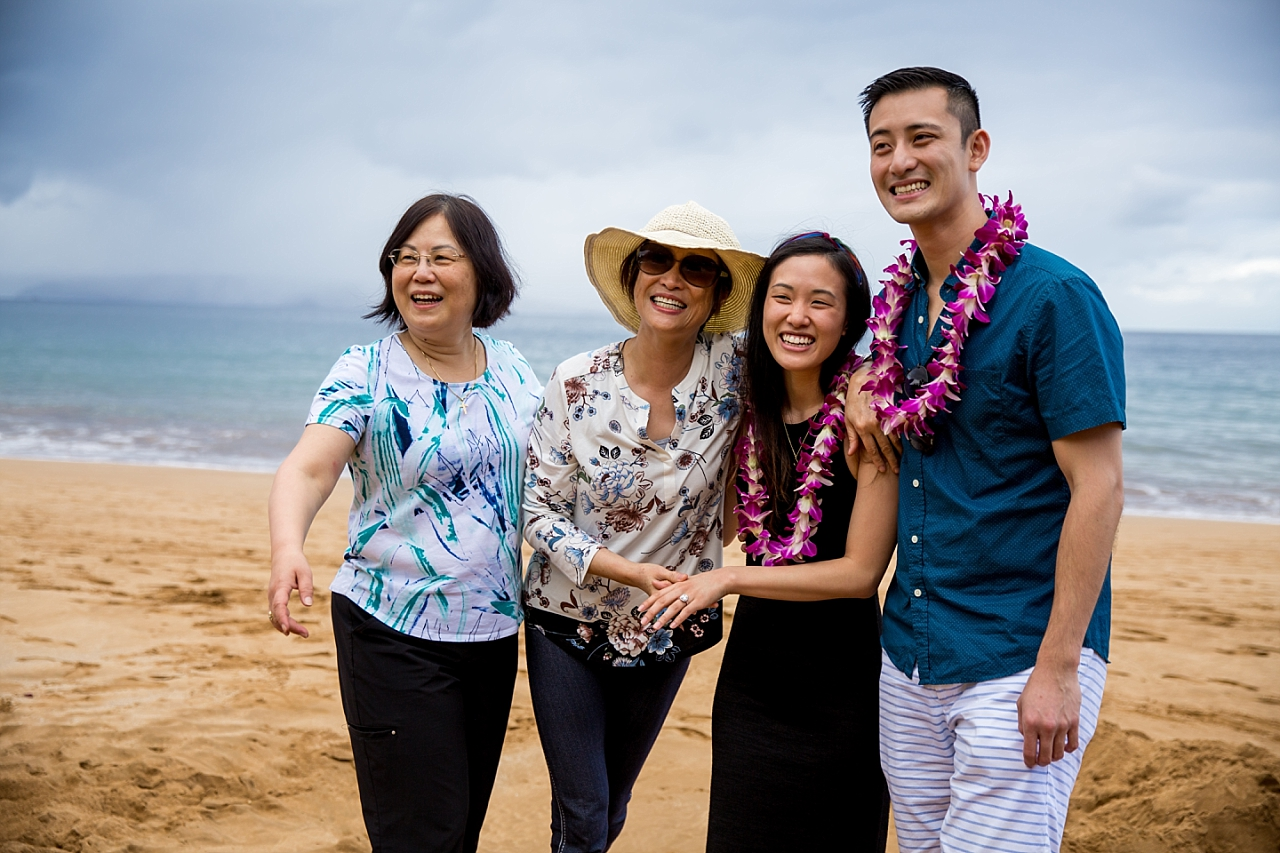 couple happily celebrating on the beach with their family after proposal