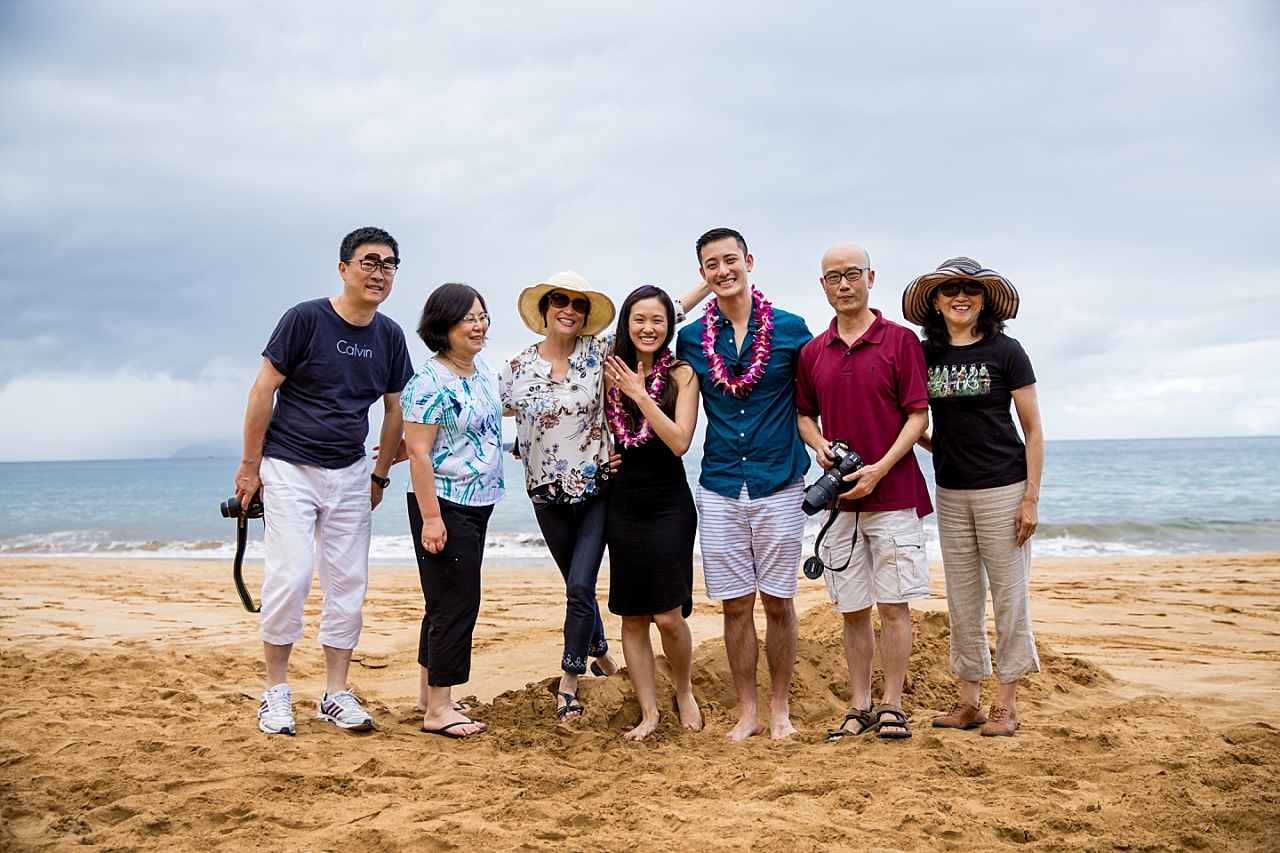 couple on the beach with their family after proposal