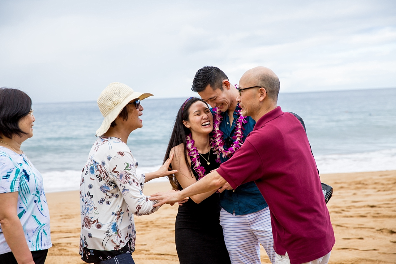 newly engaged couple hugging family on the beach in Maui