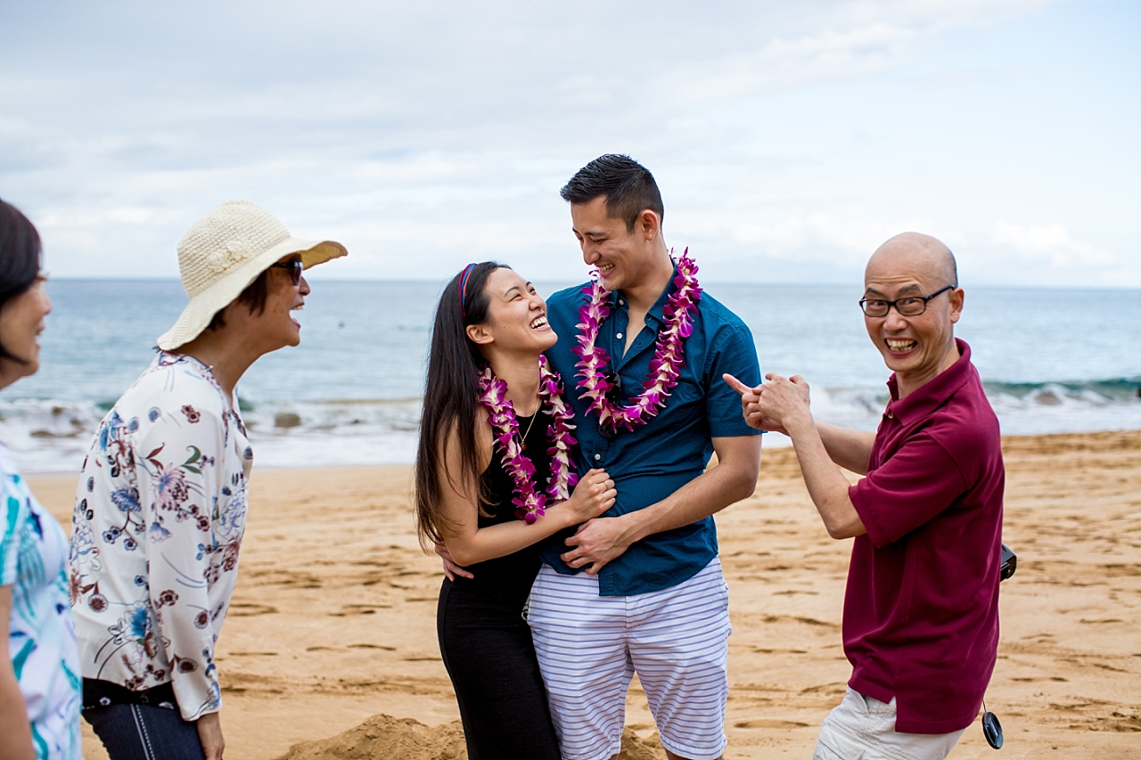 engaged couple celebrating with family on the beach in Maui