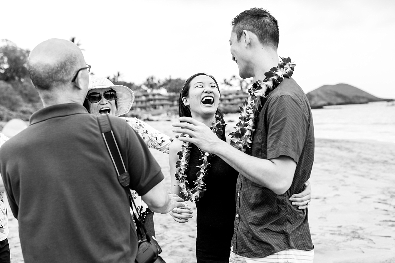 newly engaged couple celebrating with family on the beach in maui