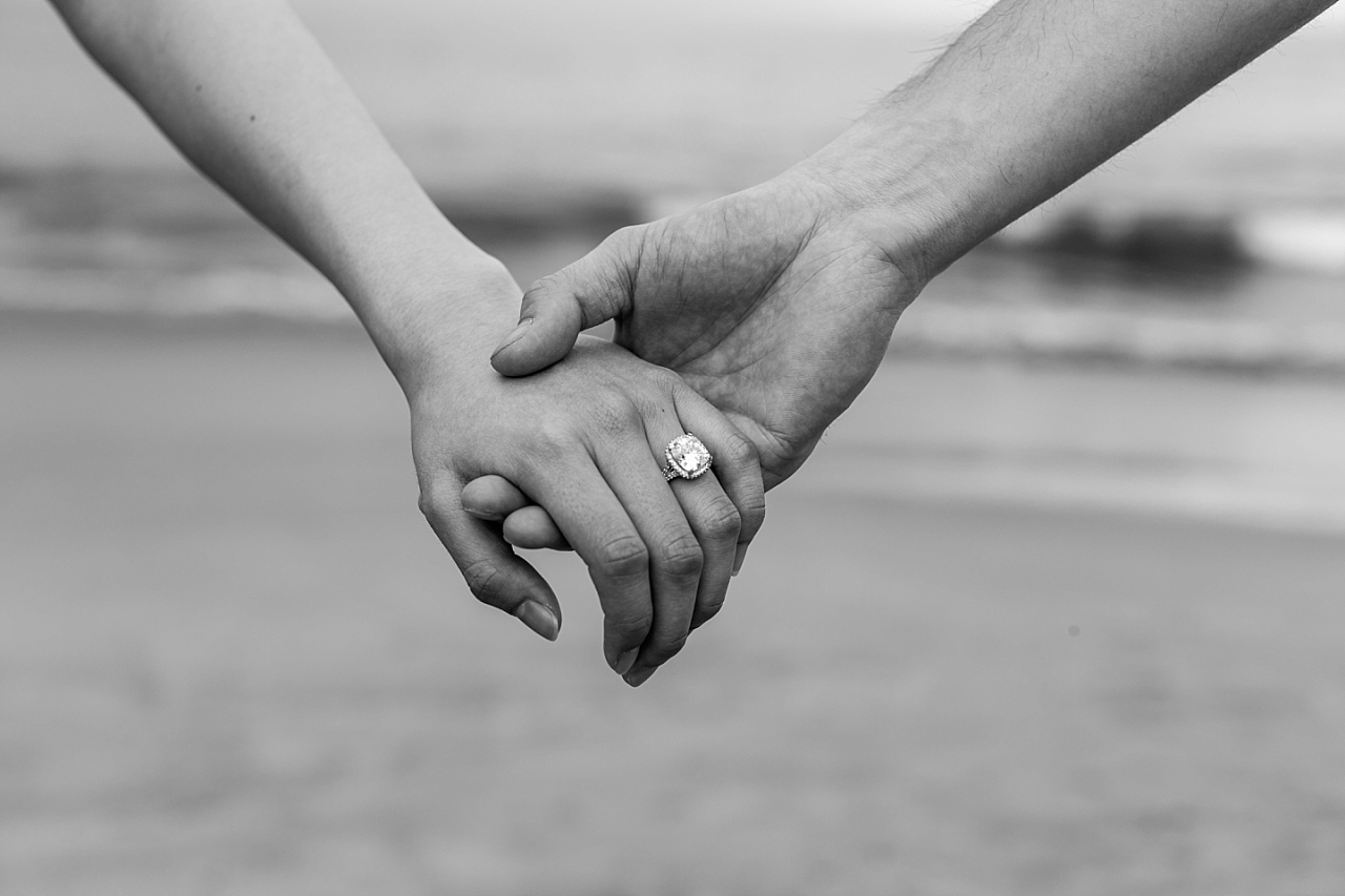 engaged couple holding hands on the beach