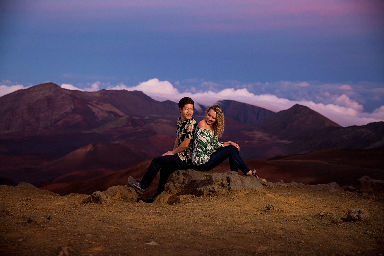 engaged couple sitting at summit of Haleakala Crater