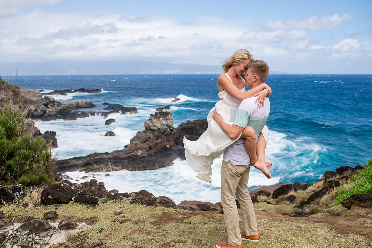 man and woman embrace on maui rock beach