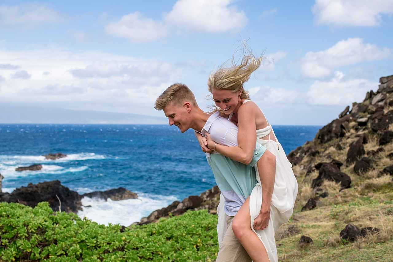 man giving woman piggy back ride on maui rock beach
