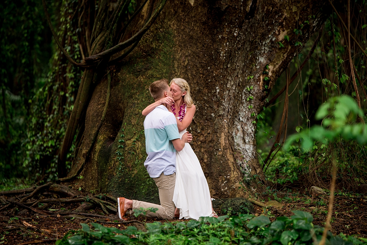 newly engaged couple kisses in maui jungle