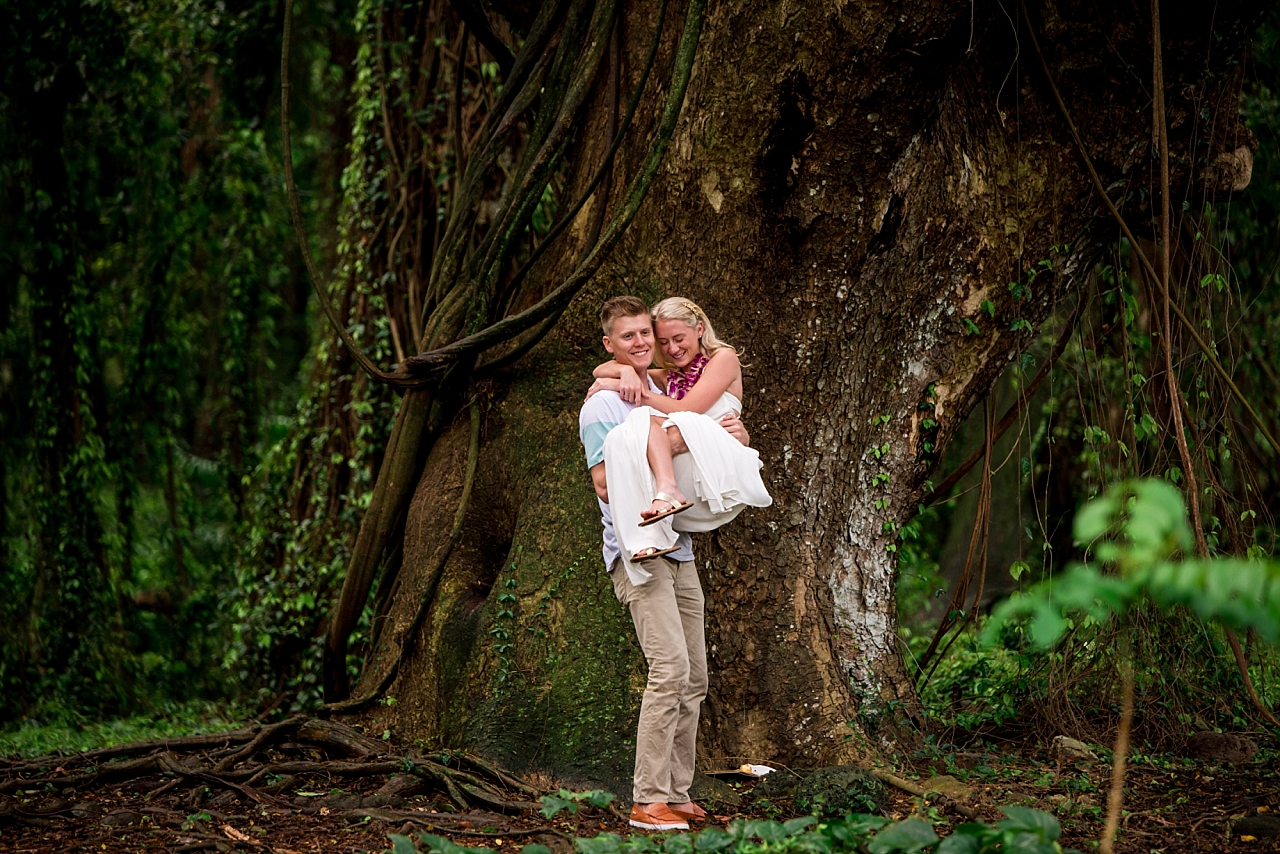 newly engaged couple hugs under tree in maui jungle
