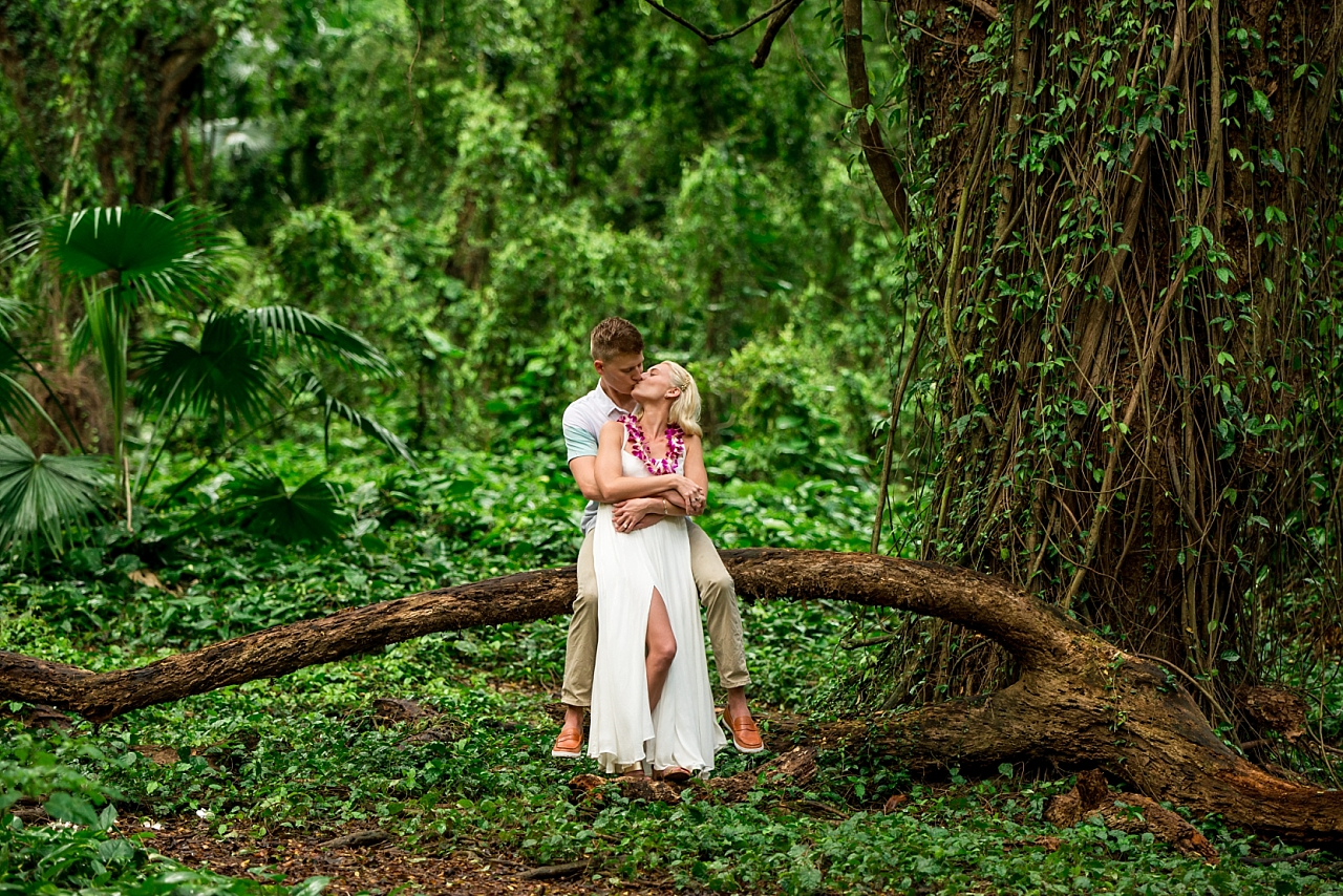 newly engaged couple sits on tree limb in maui jengle