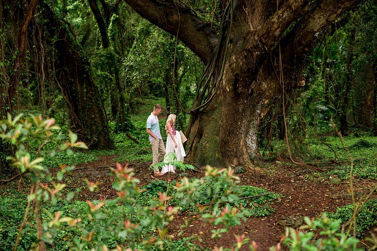 couple walks through maui jungle hand in hand