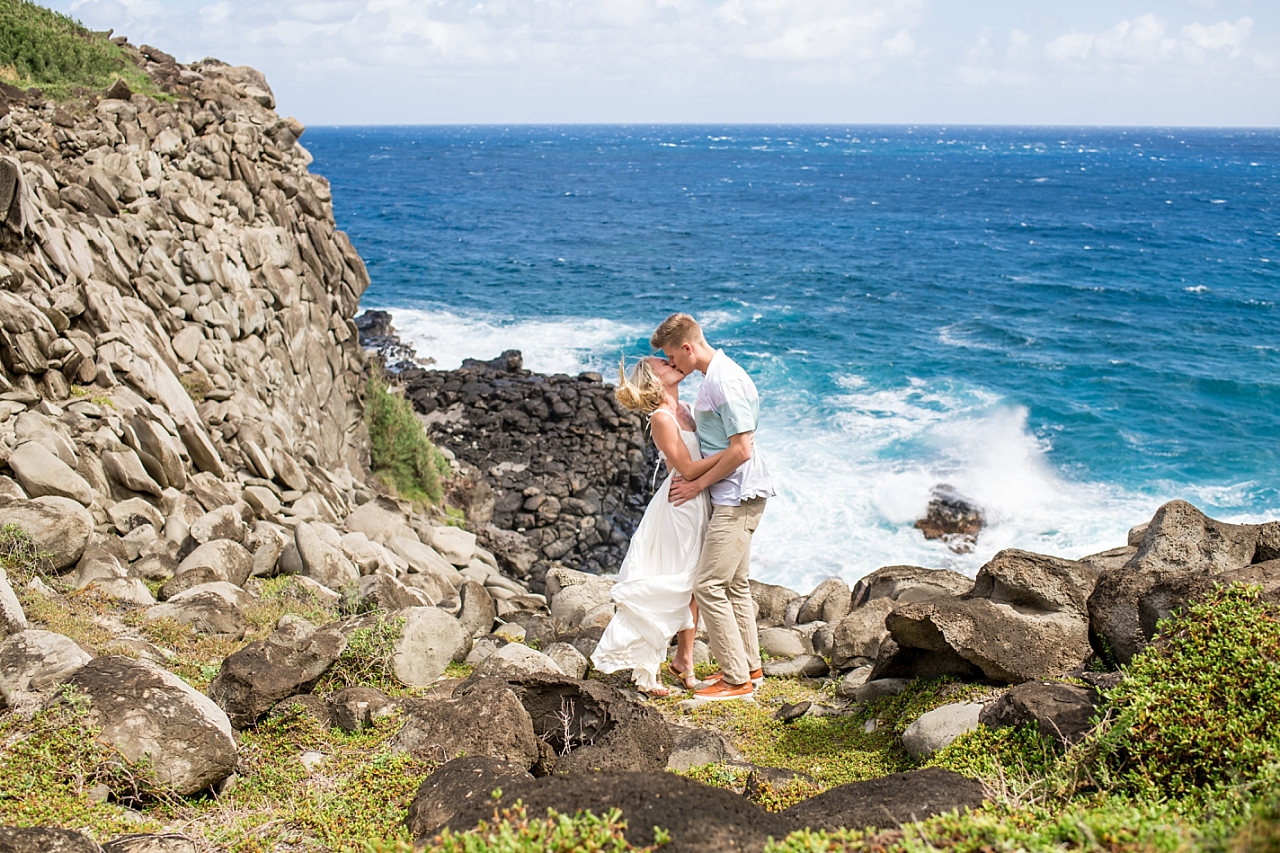newly engaged couple kissing of maui cliffs
