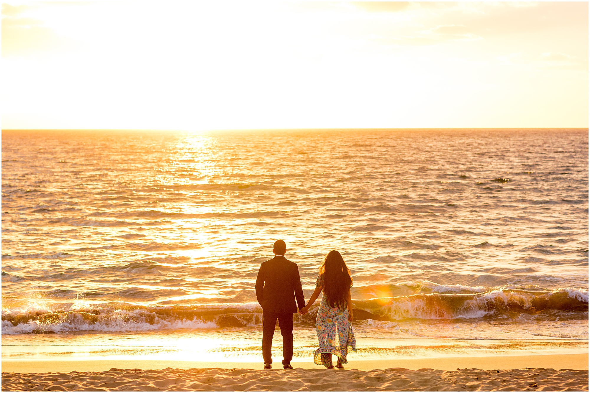 Couple facing the ocean during sunset