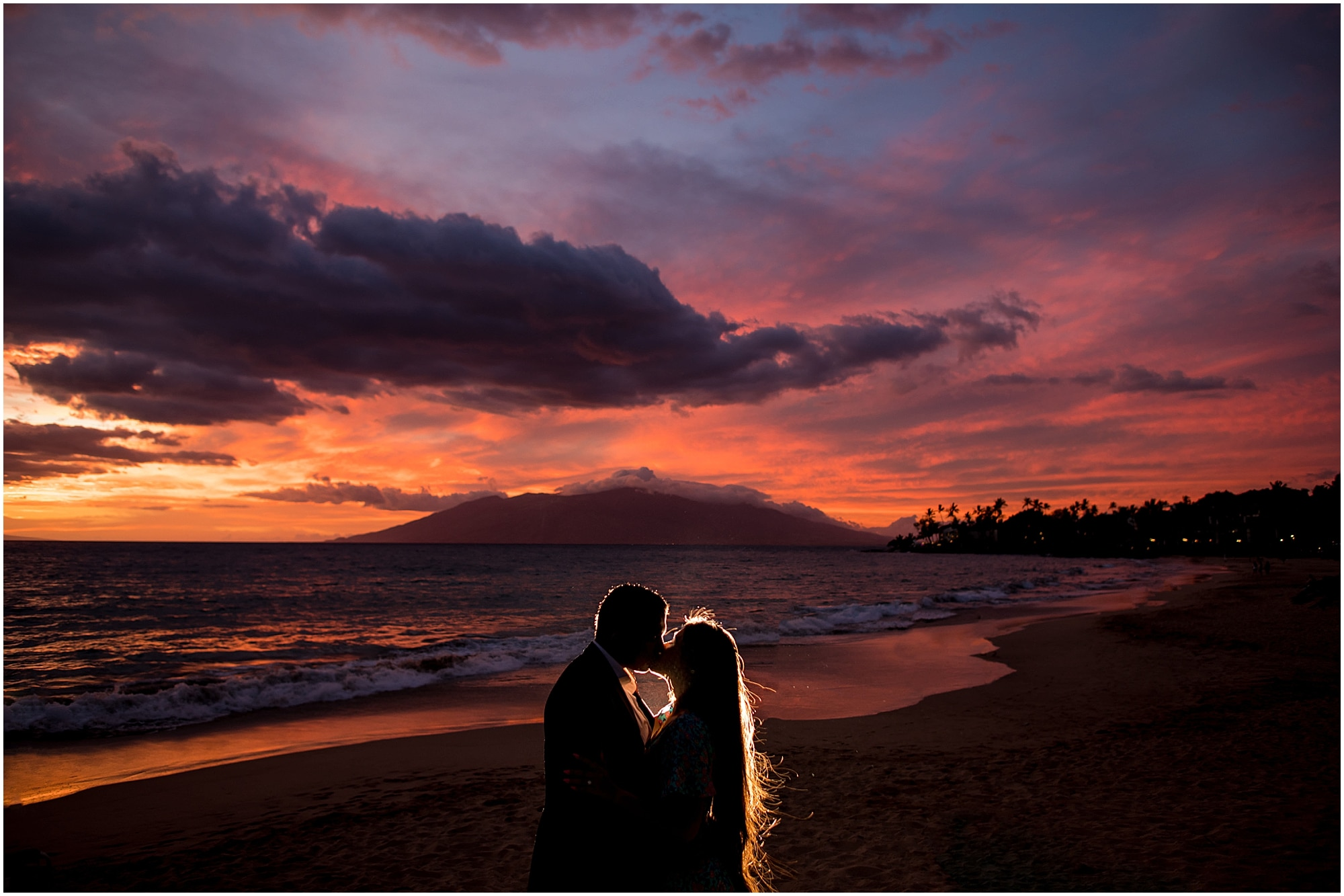 Silhouette of couple kissing on beach at sunset