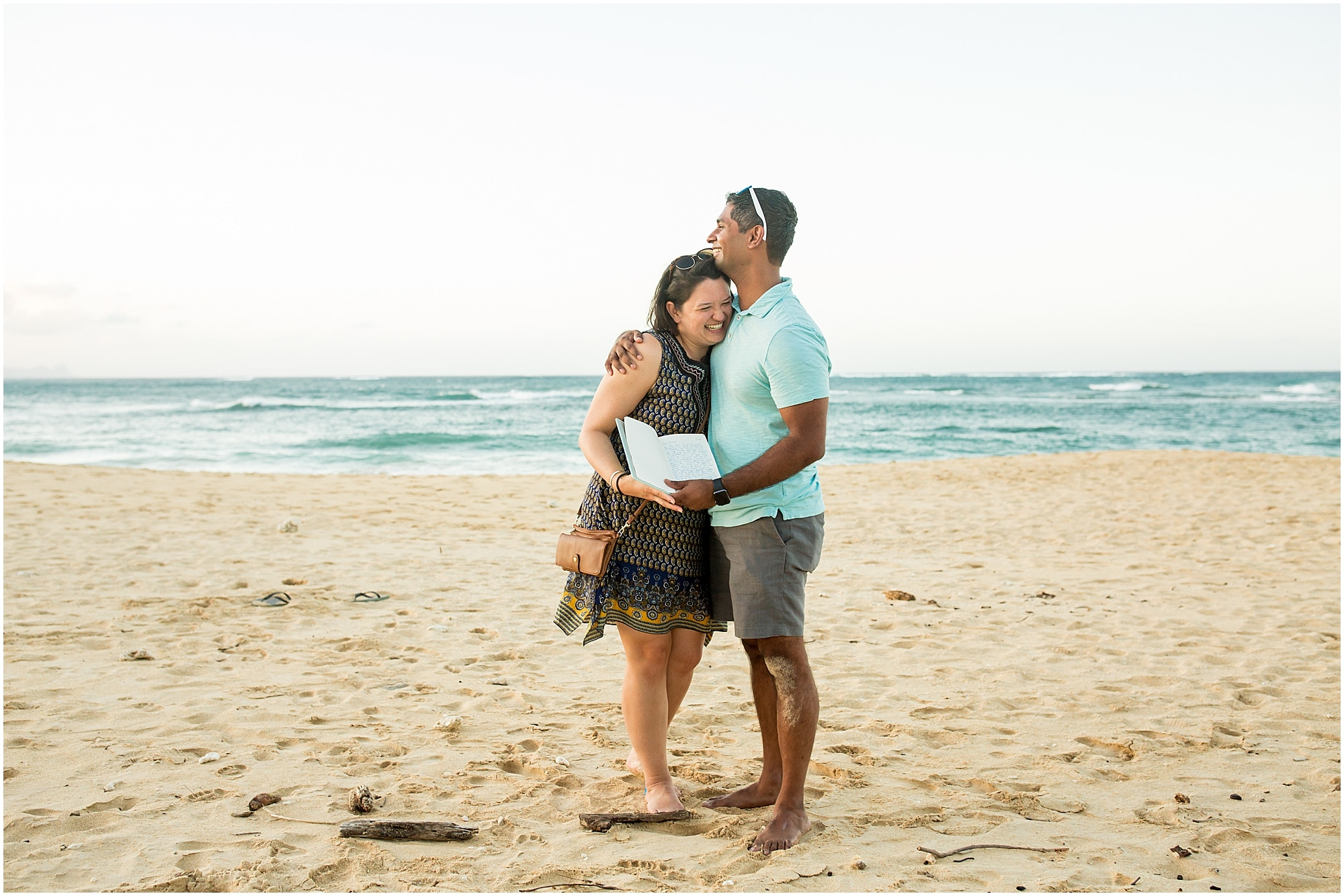 Couple holds the special book made for Maui proposal on the beach