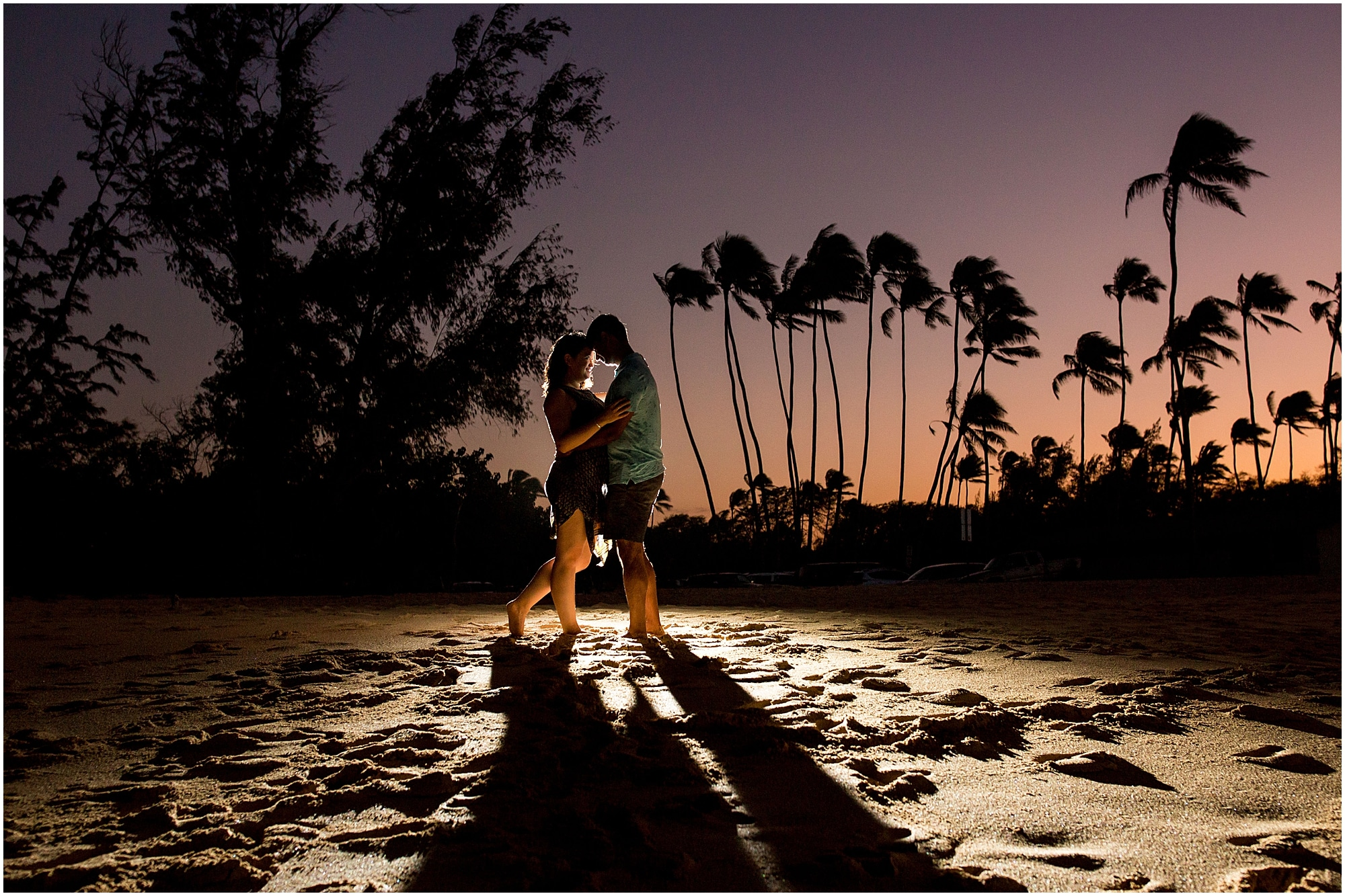 kiss on Maui beach after dusk with palm trees in the background